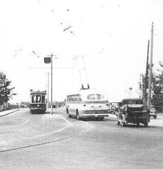 Calgary Transit - This 1947 image shows an older streetcar vehicle passing one of the new electric trolleybuses that replaced all the streetcars.