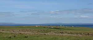 Stroma, Scotland -  alt=View looking north showing grass fields in the foreground, with ruined buildings visible in the middle distance and sea and islands visible on the horizon