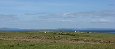 View looking north showing grass fields in the foreground, with ruined buildings visible in the middle distance and sea and islands visible on the horizon