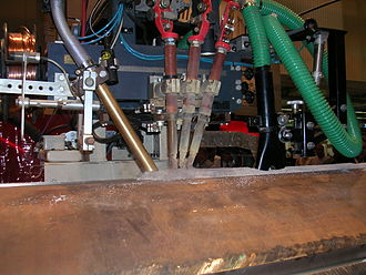 Submerged arc welding - Submerged arc welding. The welding head moves from right to left. The flux powder is supplied by the hopper on the left hand side, then follow three filler wire guns and finally a vacuum cleaner.
