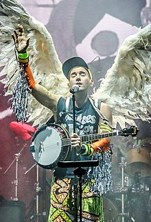 Stevens onstage with his eyes closed and hand raised in front of a microphone with a banjo slung around his shoulder and wings on his back