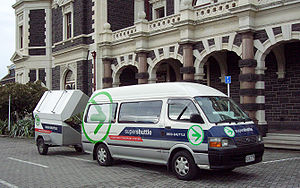 Public transport in Dunedin - A Super Shuttle service to Dunedin International Airport, operated by Tourism Transport, loads a passenger at Dunedin Railway Station