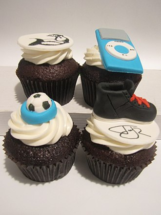 Sweet sixteen (birthday) - Chocolate cupcakes frosted with vanilla buttercream and topped with handcrafted fondant decorations for a boy's 16th birthday. Decorations include a muscular arm, an iPod, a soccer ball, and a Jay Z sneaker.
