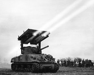 """M8 (rocket) - M8 rockets being launched from a """"Calliope"""" multiple launcher mounted on a Sherman tank."""