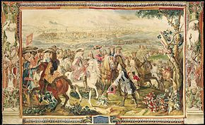Tapestry shows a crowd of men mounted on horseback. They are dressed in early 18th century style with three-cornered hats and curly shoulder-length wigs. The man in the center rides a white horse, holds a sword and wears a metal cuirass. In front of him, a man on foot has his hat off and slightly bows. A walled fortress city is in the background.