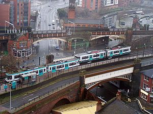 Deansgate-Castlefield tram stop - Aerial shot of two trams passing at Deansgate-Castlefield, with the line through Deansgate railway station in the background. The A56 road passes under both lines.
