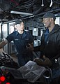U.S. Navy Boatswain's Mate 3rd Class Alonzo Bender, right, instructs Seaman Apprentice Tyler Glidden on helm operations on the bridge of the amphibious dock landing ship USS Pearl Harbor (LSD 52) during 130515-N-SP369-013.jpg