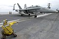 US Navy 021209-N-6895M-502 plane director guides an F-A-18 into position on the ship's flight deck.jpg