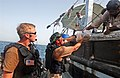 US Navy 040501-N-7586B-144 Vessel Board Search and Seizure (VBSS) Team Members from the guided missile cruiser USS Leyte Gulf (CG 55) give fruit and bread to a local fishing dhow's crew after conducting a search of the vessel.jpg