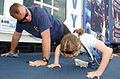 US Navy 050529-N-4729H-109 Senior Chief Aviation Ordnanceman Ron Mitchell, a recruiter for the Navy Explosive Ordnance Disposal (EOD) community, shows a young fan how to do a Navy push-up.jpg