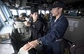 US Navy 050531-N-9851B-018 First Lieutenant, Ens. Nicholas Leshock explains the ship's compass on the bridge of the guided missile destroyer USS John S. McCain (DDG 56).jpg