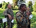 US Navy 090107-N-9995B-002 Gunnery Sgt. Ryan Tracy, left, and Sgt. Clifford Perry, assigned to Marine Corps Training and Advisory Group, observe a Jamaica Defense Force student as he practices land navigation techniques during.jpg