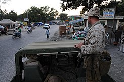 US Navy 100207-N-2735T-055 Sgt. Tom Maloney from the 24th Marine Expeditionary Unit (24th MEU) looks out at a crowded street during a reconnaissance patrol.jpg