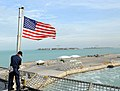 US Navy 100329-N-7653W-185 Electronic Technician 1st Class Michael Neville raises the American Flag as the Navy's newest littoral combat ship USS Independence (LCS 2) pulls pier side in Key West, Fla.jpg