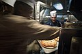 US Navy 100626-N-5319A-022 Chief Yeoman Chris Sherman assigned to Amphibious Squadron (PHIBRON) 5, removes a tray of pizzas from the oven.jpg