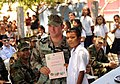 US Navy 110318-N-EC642-219 Equipment Operator 2nd Class Joseph Smittle receives a certificate of appreciation from a student at Escuela Rural Lempi.jpg