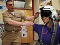 US Navy 110401-N-JD217-092 Cmdr. Roger Curry shows a student how to salute after donning a flight helmet.jpg
