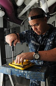 US Navy 120113-N-NB694-016 Aviation Ordnanceman Airman Moises Gonzalez replaces light bulbs in battle lanterns aboard the Nimitz-class aircraft ca.jpg