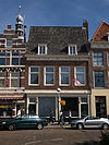 foto van Huis met lijstgevel. Langs zadeldak met twee dakkapellen. Winkelpui. Jaartal in lijstfries (Anno 1816)