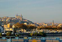 Photographie couleur prise depuis le pont Raymond-Barre. Au premier plan, l'autoroute A7. Au second plan, le clocher de Sainte-Blandine. En fond, les deux collines avec la basilique de Fourvière.