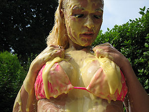 A woman covered in custard.