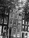 foto van Pand met zandstenen gevel onder rechte lijst met triglyfen, consoles en opzetstuk en met gebeeldhouwde versiering van de middelste vensteras