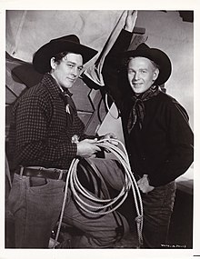 Black and white photograph showing two men standing. They are dressed in cowboy garb: jeans, kerchiefs around their necks, and cowboy hats. The man on the left is holding a lasso near his waist. A section of what appears to be a covered wagon is visible behind them.