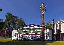 A colorful post of wood sculpted into animal faces stands in front of a wide lodge with a painted face on it