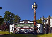 "A Kwakwaka'wakw totem pole and traditional ""big house"" in Victoria, BC."