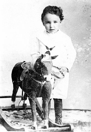 monochrome photograph of a child with a rocking horse