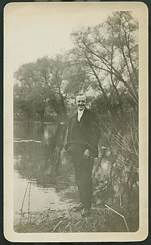 Cartheuser smiling at camera while standing at the edge of a body of water dressed in a suit and holding a hat.