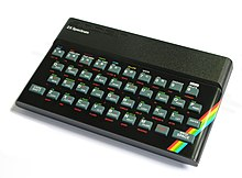 "A black, rectangular box with rounded sides. A top panel reads, in raised lettering and a robotic typeface, ""sinclair"", and below that, in modern, white lettering, ""ZX Spectrum"". A full QWERTY keyboard with Chiclet buttons, full number set, and buttons for Enter, Caps Shift, and Space. Each of the buttons has alternative text in green and red lettering nearby, to access other functions when the corresponding modifier key is pressed. A red, yellow, green, blue rainbow streak shows in the right corner, but rest of the machine is black."