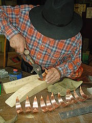 Zingueur en cours de fabrication d'une girouette en cuivre.