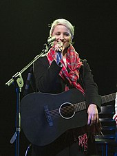 Dianna Agron, smiling in a warm coat and scarf, holds a microphone and a black guitar while on a stage.
