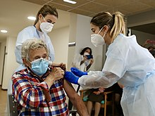 Elderly woman roles up sleeve as two nurses administer a vaccine