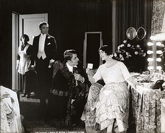 Lina Cavalieri - In the silent drama A Woman of Impulse, Lina Cavalieri receives Raymond Bloomer, on one knee, and Robert Cain, in evening dress.