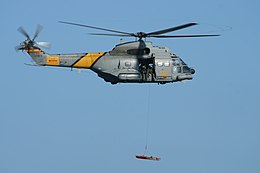 "Spanish Air Force Aérospatiale SA330J Puma of 801 Squadron flying in an airshow. It is lifting a stretcher with a hoist. On the side of the helicopter is lettering reading ""SAR"", in yellow against the military grey color scheme."