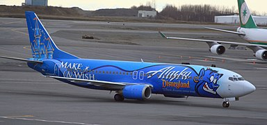 An aircraft painted dark blue with a genie on the fuselage and a castle on the tail, taxiing on the tarmac with another aircraft and some trees in the background.