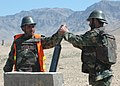 An Afghan National Army mortar instructor assists a trainee to properly insert an 82 MM Russian Mortar (4706039208).jpg