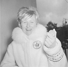 A woman with short blonde hair wearing a thick fur coat bearing a maple leaf and Olympic rings. She displays a large smile as she holds up an Olympic medal.
