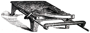 Cross-hatched image of a flat platform on four short legs with a guillotine-blade at one end.