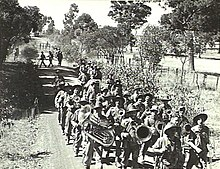 Soldiers marching along a dirt road in the Australian bush, led by a brass band