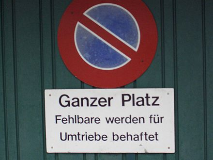 "An example of Swiss Standard German used for a ""no parking"" sign. Fehlbare werden für Umtriebe behaftet would rather be expressed as Zuwiderhandelnde haften für die Kosten des entstehenden Aufwands in German Standard German. ""Fehlbare"" (as used in this context), ""Umtriebe"", and ""behaftet"" are Helvetisms."