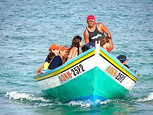 A group of people riding a wooden boat off a b...