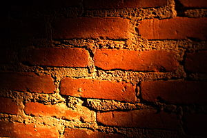 A brick wall partially illuminated by a ray of...
