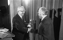 Walter Hallstein on stage, shaking hands while receiving prize.
