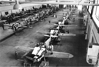 Military production during World War II - Assembly line of Messerschmitt Bf 109G-6s fighters in a German aircraft factory.