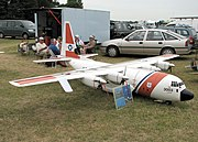 A very large US Coastguard C-130J Hercules flying model. The wingspan is 18 feet 6 inches (5.6 m). The crew of five who fly and maintain it are in the background.