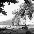 COLLECTIE TROPENMUSEUM Het 83-jarige hoofd van het dorp zit gehurkd bij de rotsen die voornamelijk bestaan uit een goede kwaliteit tras aan de kust van Poelau Lembeh Celebes TMnr 10004402.jpg