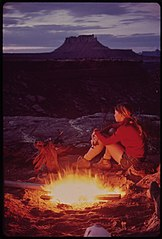 Camping in the Maze, a Remote and Rugged Region in the Heart of the Canyonlands. Because It Seldom Rains, Tents Are Not Necessary. Firewood Is Dry and Plentiful. Ekker Butte Rises in the Background, 05-1972 (3814166145).jpg